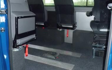 Gulv med sort, fuldlimet tæppe. 4 drejeklapstole, Jany type 862.  Elkørestolslås for kørestol uden passager.