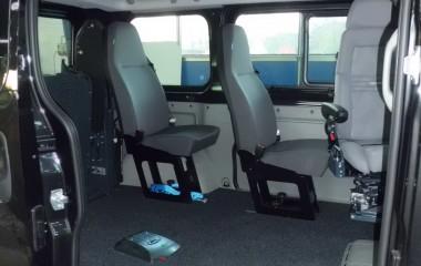 Gulv med sort, fuldlimet tæppe. To passagersæder af typen Jany 801. Elkørestolslås for kørestol uden passager.