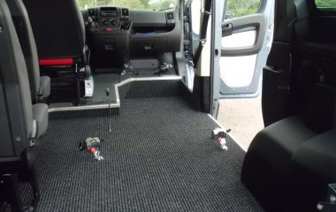 Bundsænkning i højre side for at kørestolen kan køre helt frem. Retractor kørestolsbespænding og gulv med fuldlimet tæppe afsluttet med aluliste for at undgå slitage.