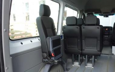 Martech Turny drejeklapstol monteret på bom over baghjulskasse i en Mercedes Sprinter. Særlige features: Justerbart ryglæn, højdejusterbar nakkestøtte og plastbagbeklædning på stolryg gør stolen slidstærk.