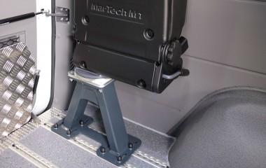 Martech Turny drejeklapstol monteret på fod i alugulv i en Mercedes Sprinter. Særlige features: Justerbart ryglæn, højdejusterbar nakkestøtte og plastbagbeklædning på stolryg gør stolen slidstærk.