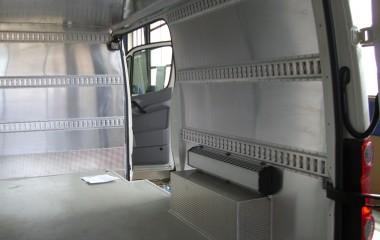 Vandttæt og hygiejnisk aluminiumsbeklædning på sider, døre og loft. Isolerede sider og loft. Baghjulskasser beklædt med aluriskornsplade og radiator monteret over disse.
