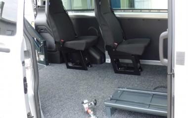 Gulv med sort, fuldlimet tæppe. To passagerstole af typen Jany 801. Retractor kørestolsbespænding.