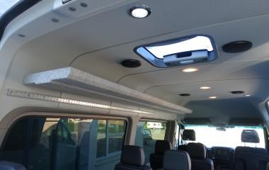 Taglem, højtalere, bagagehylde og Unwin aluskinner til montering af skulderseler til kørestolsbruger monteret med lovpligtige forstærkninger over sideruder.