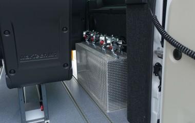 Hjulkassebeklædning i bag fremstillet af riskornsplade i aluminium for at gøre bedre plads til kørestole. Hjulkassen fungerer også som opbevaringsplads for kørestolsbespænding.