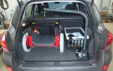 Kørestolskran med løftekapacitet på 35 kg monteret i bagagerum for løft af Carony Classic kørestolsunderstel.